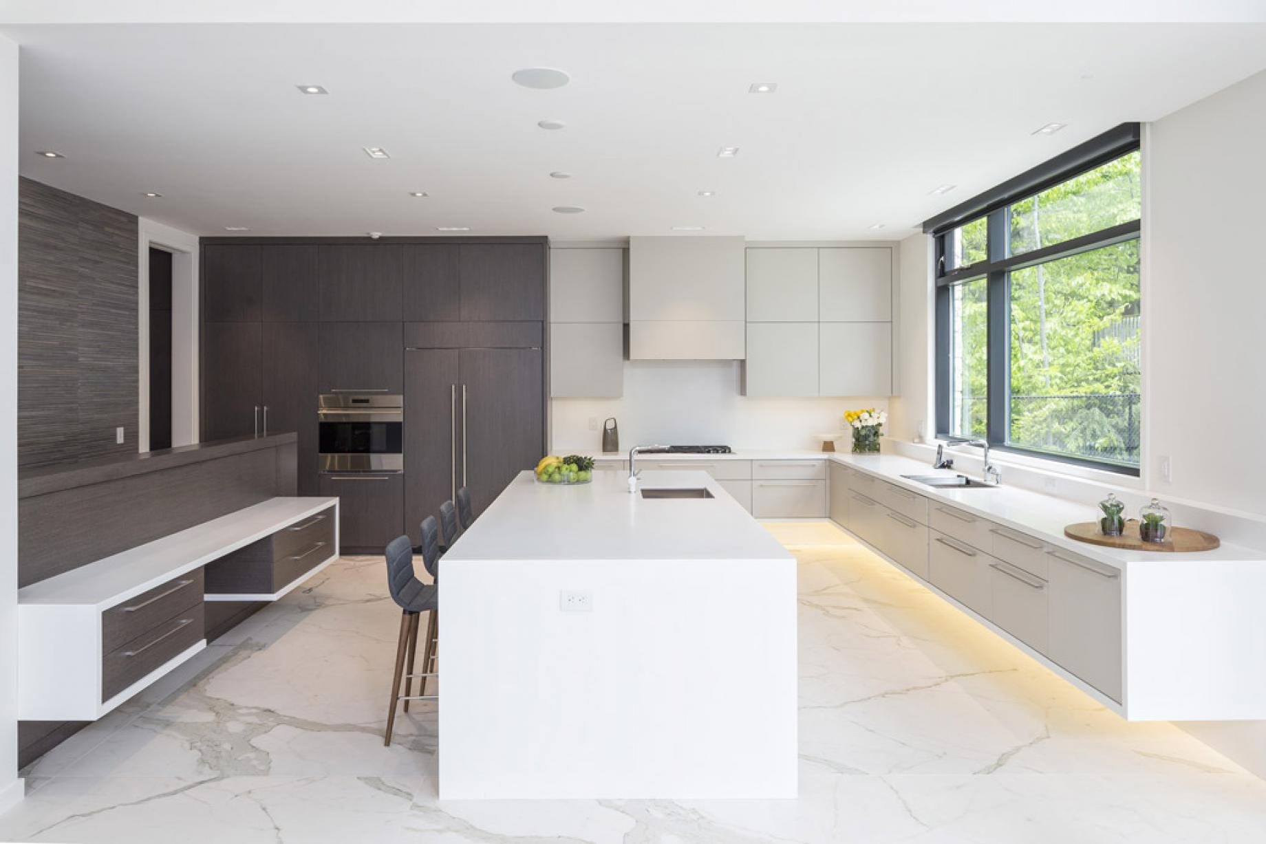 The kitchen in the Glass House features a huge island and modern appliances