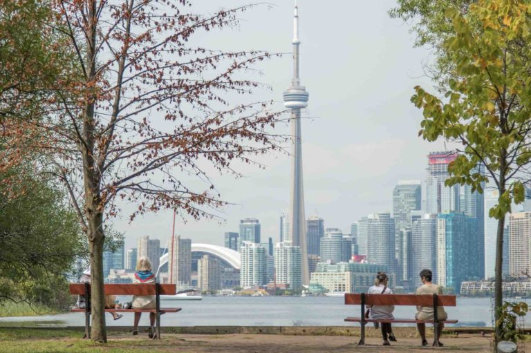 Toronto destination city sky;line park with people on benches