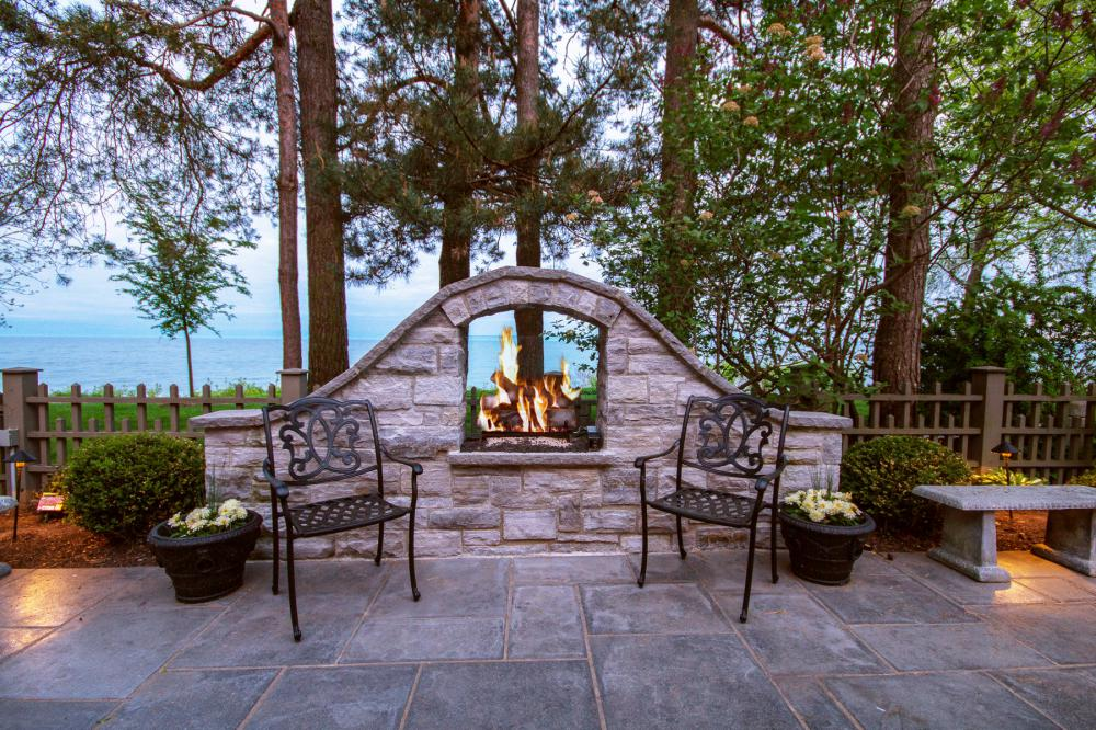 Luxury Oakville real estate showing home's patio overlooking lake and firepit