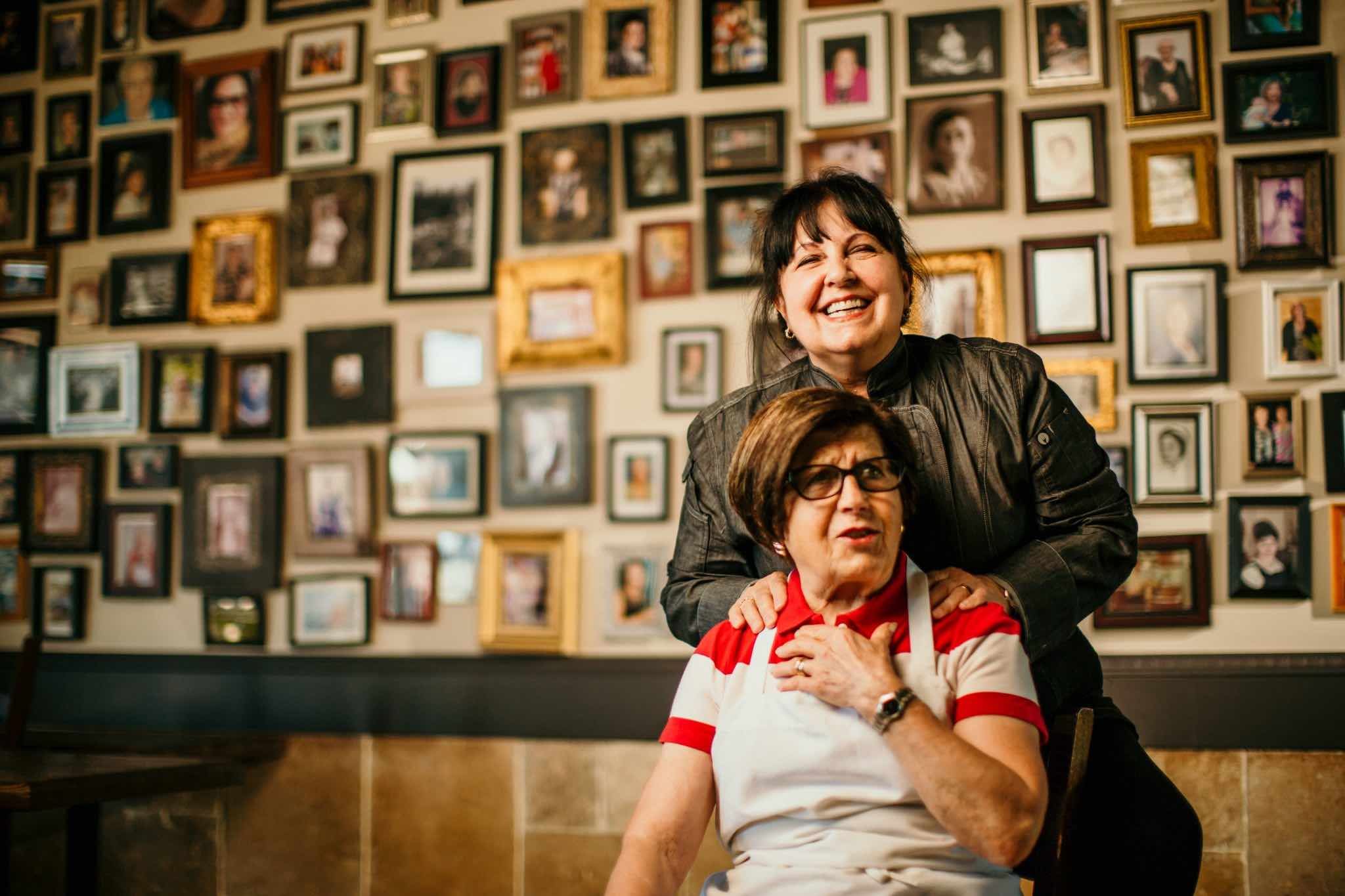 Ritorno's mother and daughter team standing in front of wall with photos